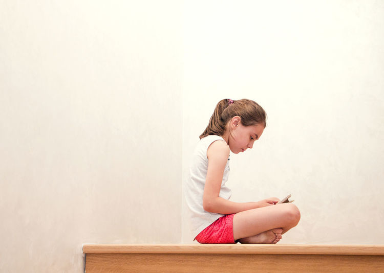 Side View Of Girl Sitting Against Wall At Home
