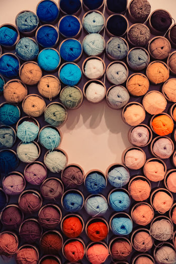 Circular placement of colorful yarn threads for stitching in a sewing shop. Colors Colorful Stitching Sewing Weaving Circle Yarn Teal Red Orange Color Yellow Pink