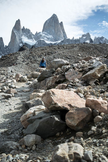 Woman on rocks by snowcapped mountains against cloudy sky