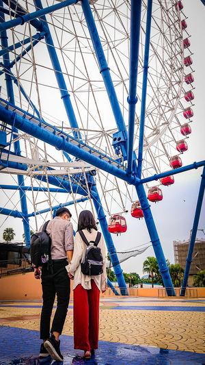 Rear view of couple walking in amusement park