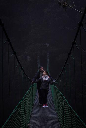 Couple standing on footbridge