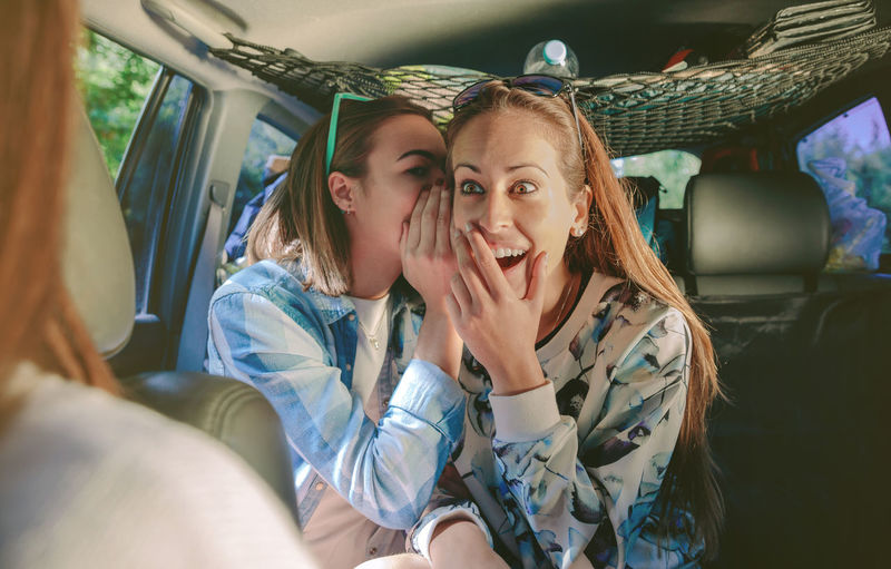 Surprised woman laughing to listening gossip of her friend sitting in rear seat of car Friends Fun Gossip Horizontal Nature Passenger Travel Trip Woman Caucasian Cheerful Crazy Friendship Girl Inside Leisure Lifestyles Real People Roadtrip Rumor Secret Surprise Togheter Two People Vehicle Interior