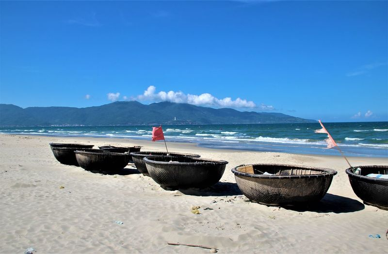 Traditional fishingboats on a deserted beach in the mid day heat Sea Beach Water Sky Blue Sunlight Outdoors Mountain Fishing Boats Beauty In Nature No People Tranquil Scene Nautical Vessel Mode Of Transportation Da Nang, Vietnam Scenics - Nature Landscape_Collection Landscape_photography