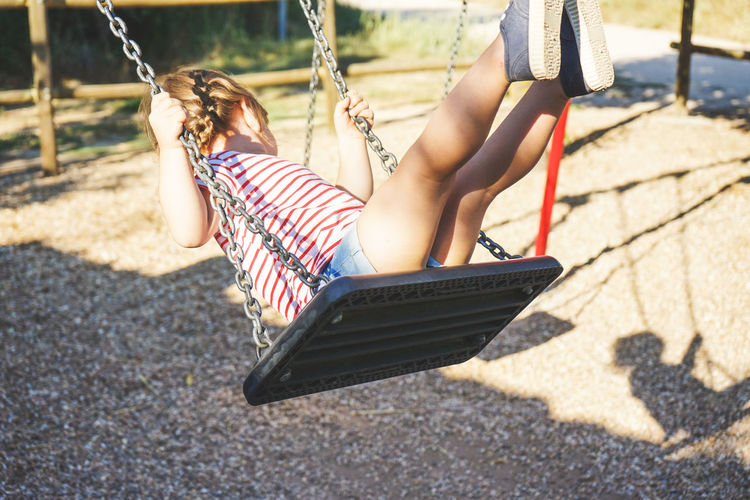 Swing Playground Child Sunlight Childhood Striped Nature Day Girls Shadow One Person Leisure Activity Full Length Fun Females Casual Clothing Real People Hanging Outdoors Innocence Outdoor Play Equipment