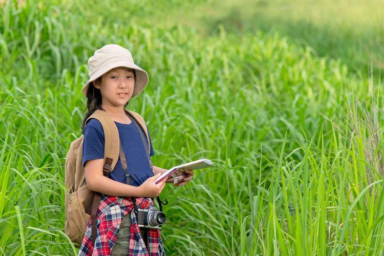 Full length portrait of girl standing on field