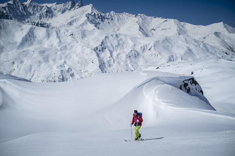 Man skiing on snowcapped mountains during winter