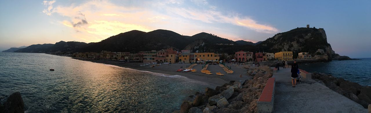 sea, water, sky, sunset, mountain, nature, beauty in nature, scenics, outdoors, cloud - sky, dusk, mountain range, beach, real people, architecture, built structure, building exterior, large group of people, wave, day, people