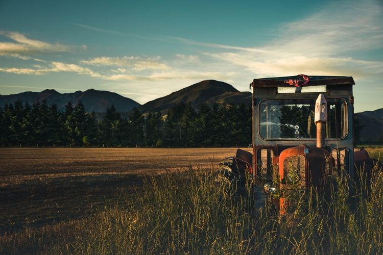 Abandoned Tractor On Grassy Field Against Mountains During Sunset