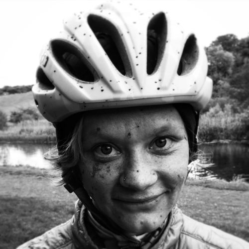 Portrait of young woman wearing cycling helmet against lake