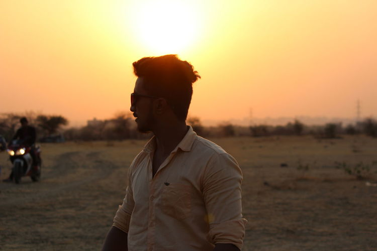 Man looking away while standing on land against sky during sunset