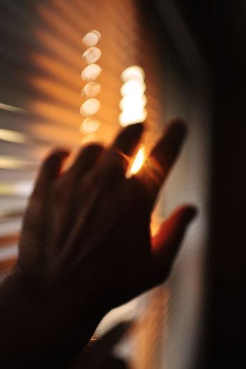 Close-up of hand on illuminated lamp