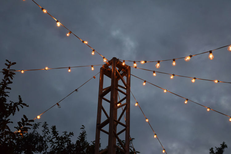 Low Angle View Of Illuminated Lights Against Sky At Dusk