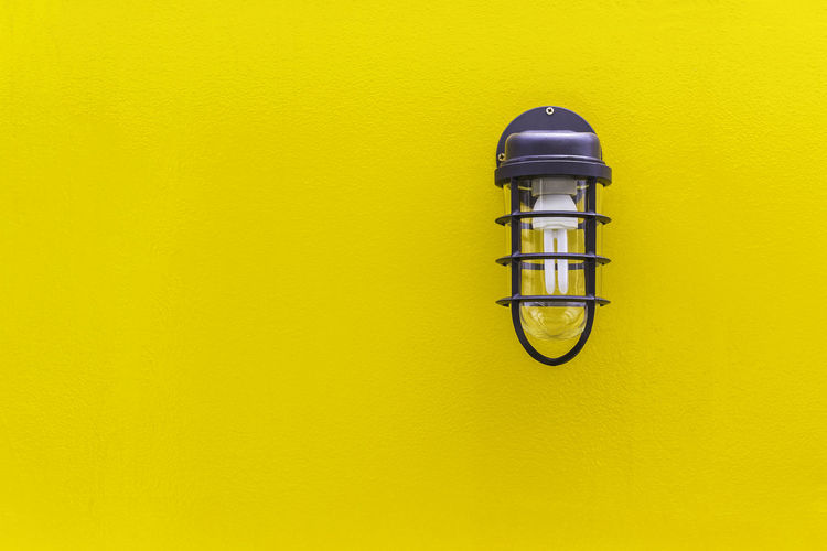 Close-up of gas light on yellow wall