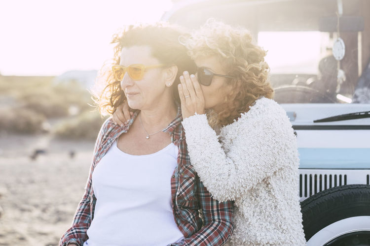 People traveling together - couple of caucasian curly friends women whispering at the ear some secrets with sunny sunset in backgorund - old vintage van for alternative travel vacation concept Leisure Activity Lifestyles Real People Women Focus On Foreground Waist Up Adult Casual Clothing Young Women Standing Day Two People Nature Transportation Hair Togetherness People Young Adult Emotion Positive Emotion Hairstyle Outdoors Couple - Relationship Traveling Friends Secret Backgrounds Beach Nature Old Van Caravan Curly Hair Caucasian Sunset Gossip Message