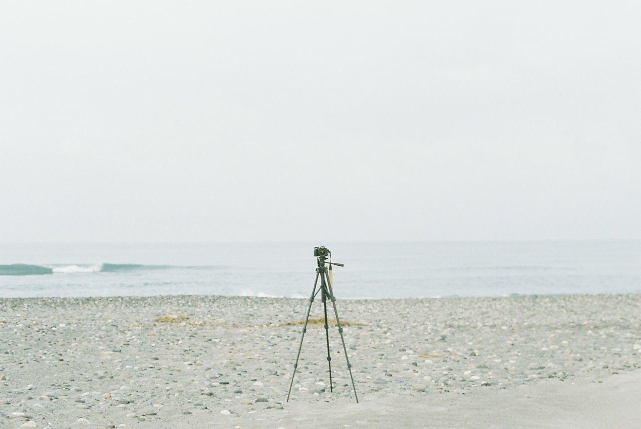Camera on tripod at beach against clear sky