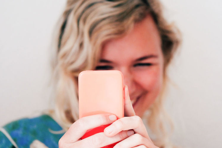 Smiling young woman using mobile phone at home