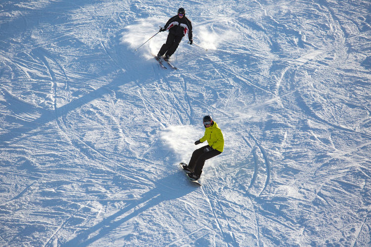 High angle view of people skiing and snowboarding on snow