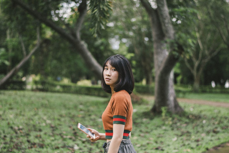 Portrait of young woman holding mobile phone while standing against trees in park