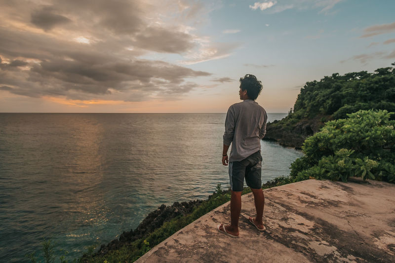 Rear view of man standing by sea against sky during sunset