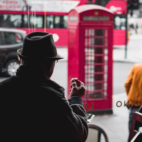 Watching London whilst eating cake EyeEm LOST IN London London Trafalgar Square Real People Red Rear View Building Exterior Day Lifestyles Warm Clothing Outdoors City Built Structure Technology One Person Architecture Postcode Postcards