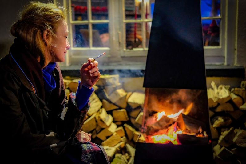 Woman smoking cigarette by bonfire at night