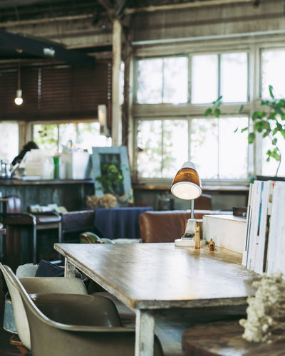 Table Seat Indoors  Chair Day Business Food And Drink Focus On Foreground No People Restaurant Wood - Material Absence Still Life Kitchen Household Equipment Window Furniture Freshness Domestic Room Electric Lamp