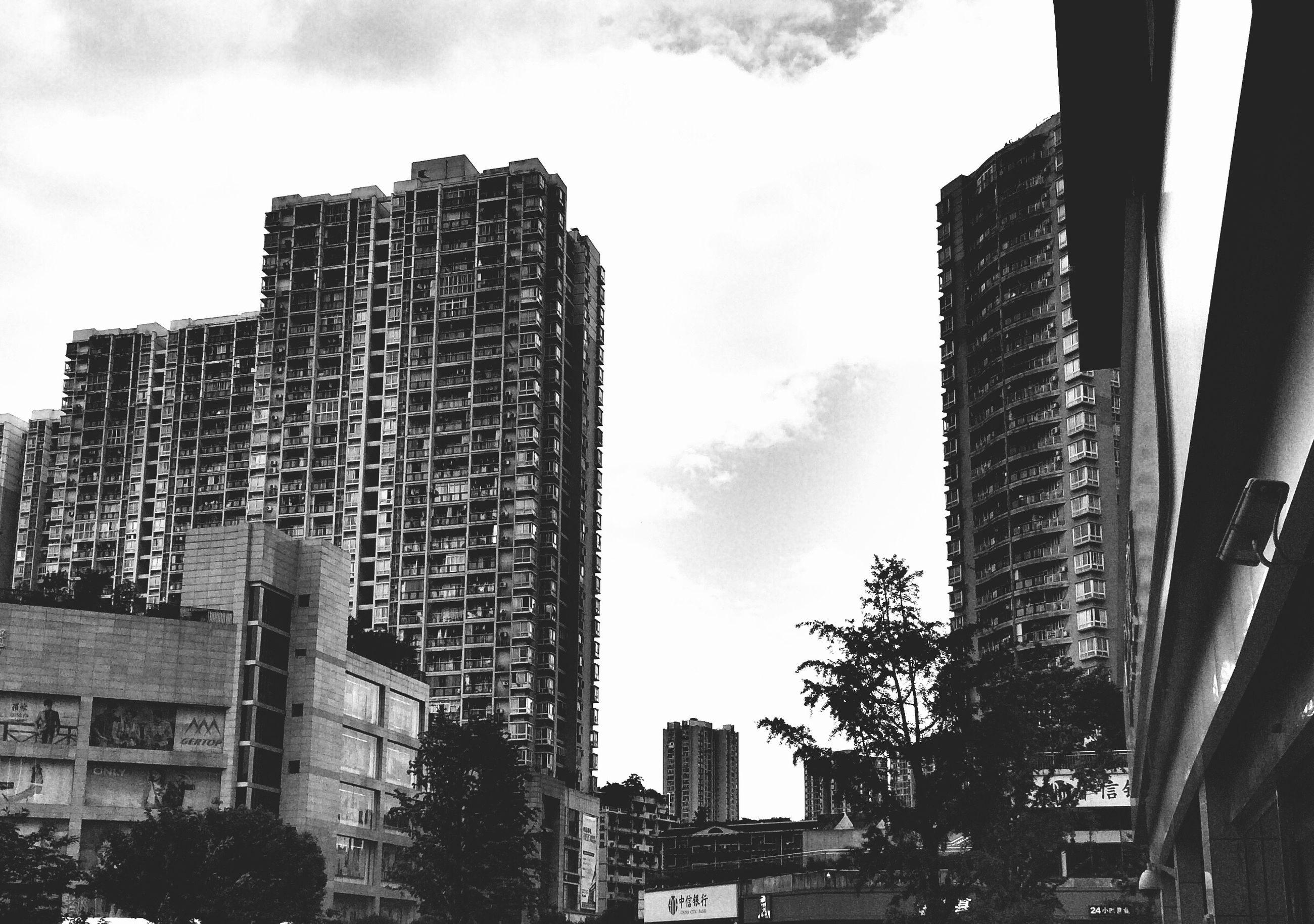 building exterior, architecture, built structure, low angle view, sky, city, building, tree, residential building, residential structure, cloud - sky, window, day, tall - high, outdoors, no people, office building, skyscraper, city life, cloud