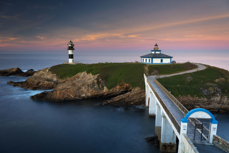 Lighthouse by sea and buildings against sky during sunset