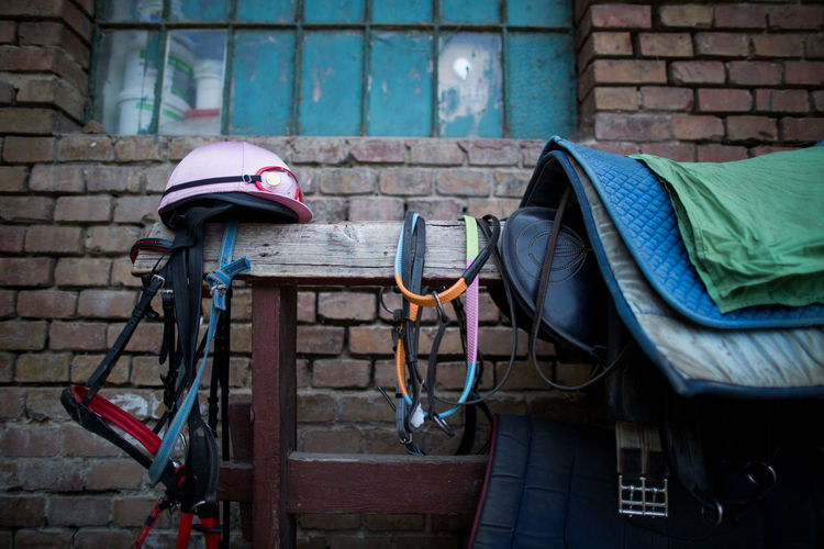 Saddles And Bridles With Helmet On Wood Against Stable
