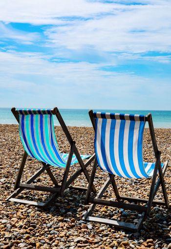 Deck chairs on beach against sky