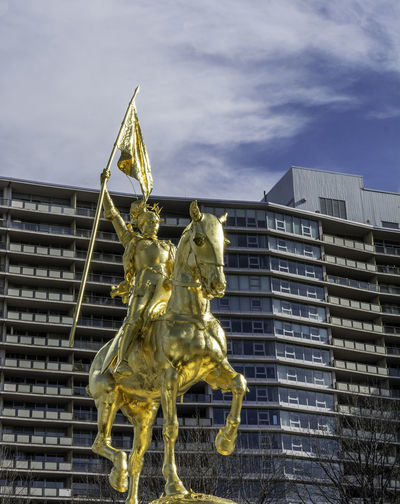 Low angle view of gold statues against building in city