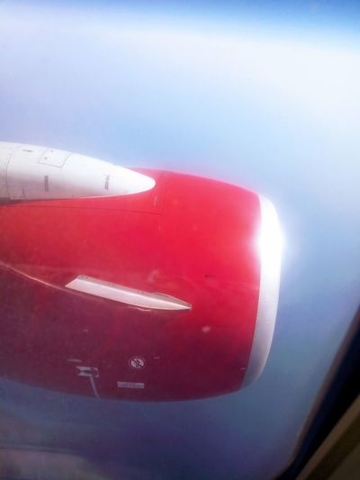 Close-up of red airplane flying against sky