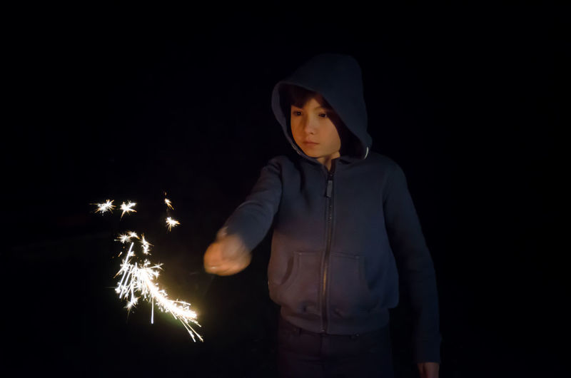 Cute Boy Holding Sparkler While Standing Over Black Background