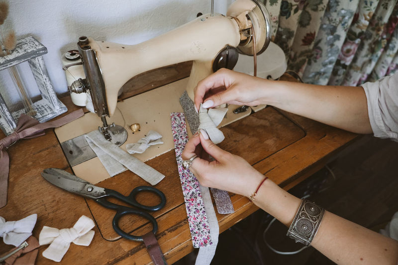 Cropped hand of woman using sewing machine