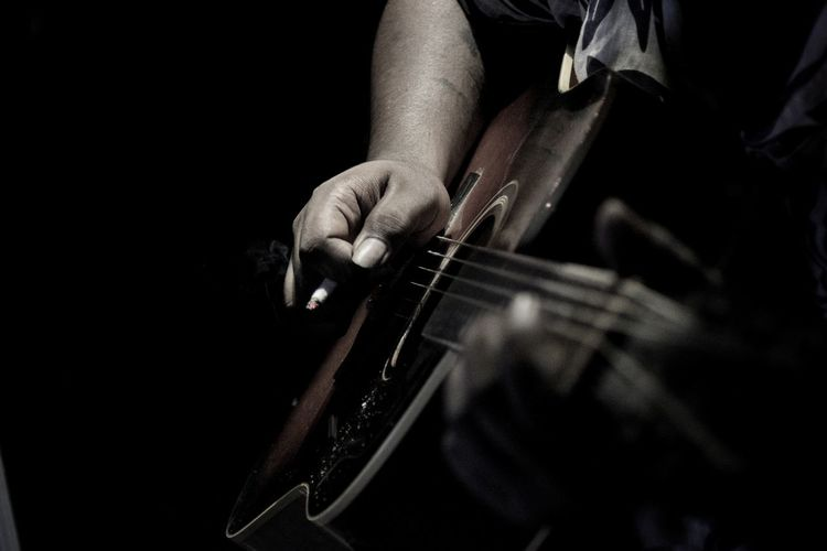 Midsection of man playing guitar over black background