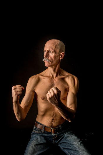 Senior fighter practicing against black background