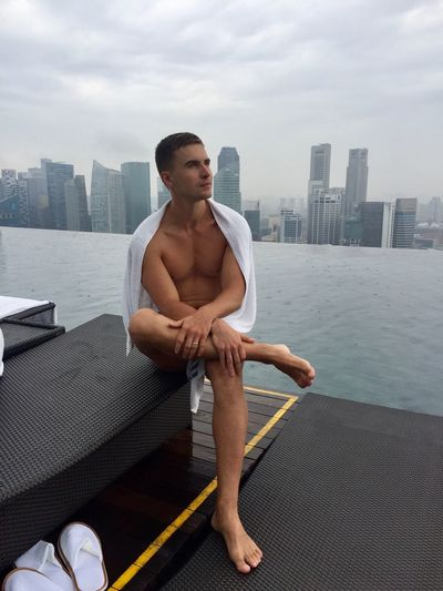Thoughtful man looking away while sitting by infinity pool against buildings in city