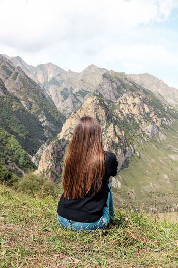 Rear view of woman looking at mountains against sky