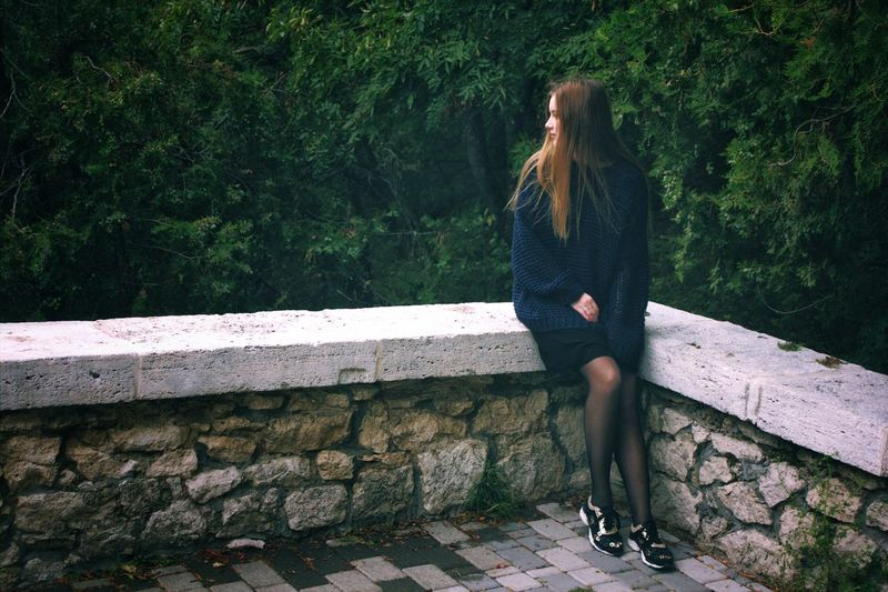 Full length of young woman sitting on retaining wall against trees