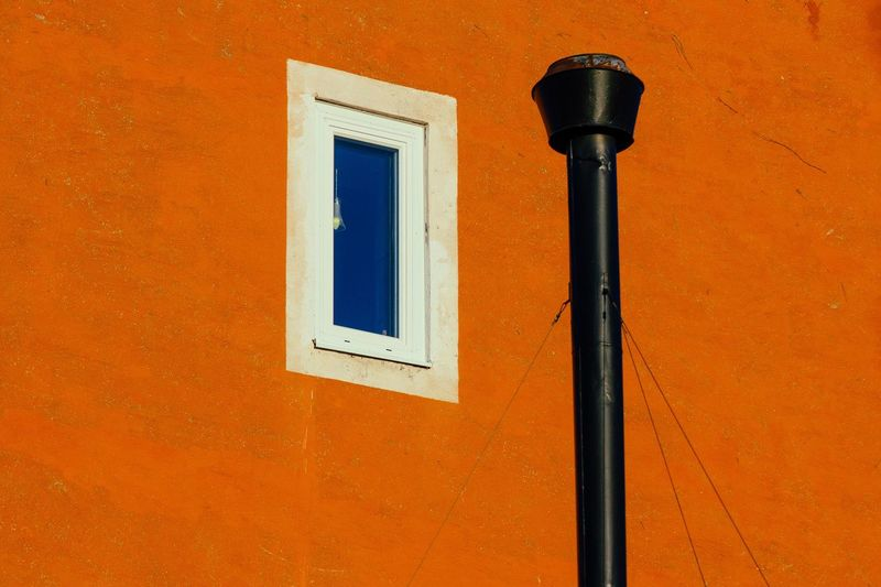 Close-up of window against orange wall