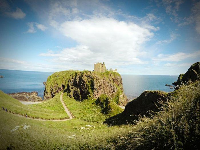 Dunnottar castle by sea against sky