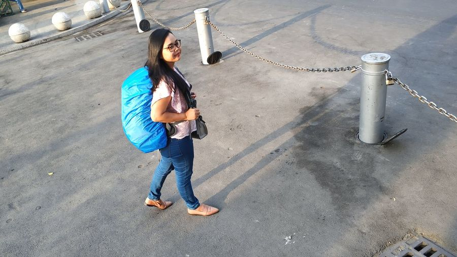 High angle view of young woman standing with backpack on road