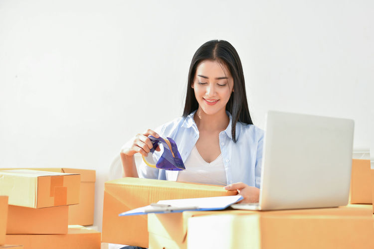 Young Businesswoman Packing Holding Box While Sitting On Bed
