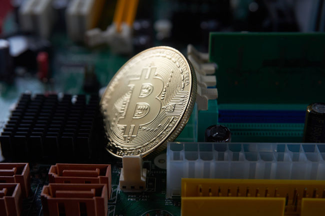 A close up of golden bitcoin on the computer motherboard. Currency Gold Wallet Bitcoin Coin Block Chain Blockchain Cryptocurrency Cryptography Digital Currency Money Motherboard Purse Silver  Technological Technology Transaction