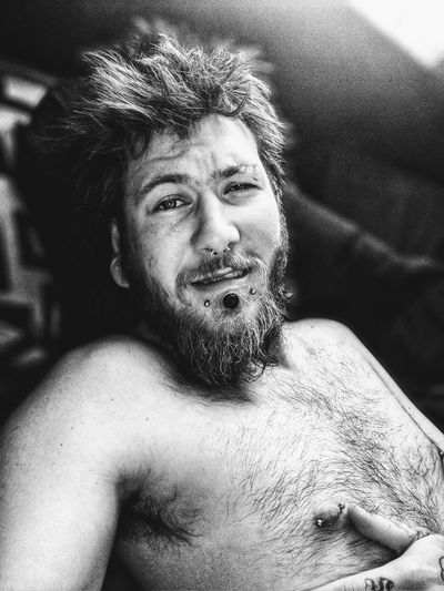 Portrait of shirtless man lying on bed