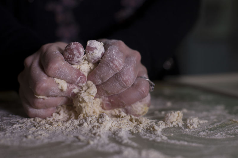 Cropped hands of woman kneading dough
