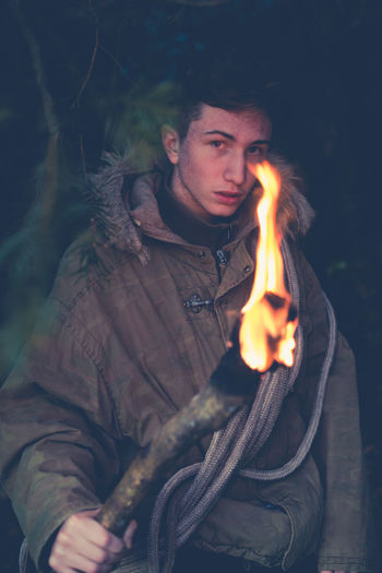 young boy explorer with torch in hand Exploring Adventure Adventure Time Burning Cave Explorer Flame Leisure Activity Lifestyles Looking At Camera Nature One Person Outdoors People Real People Torch Warm Clothing An Eye For Travel Go Higher