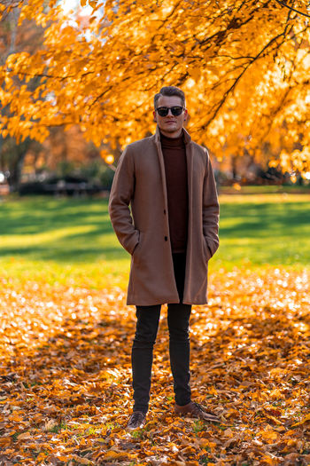 Full length portrait of young man standing against trees during autumn