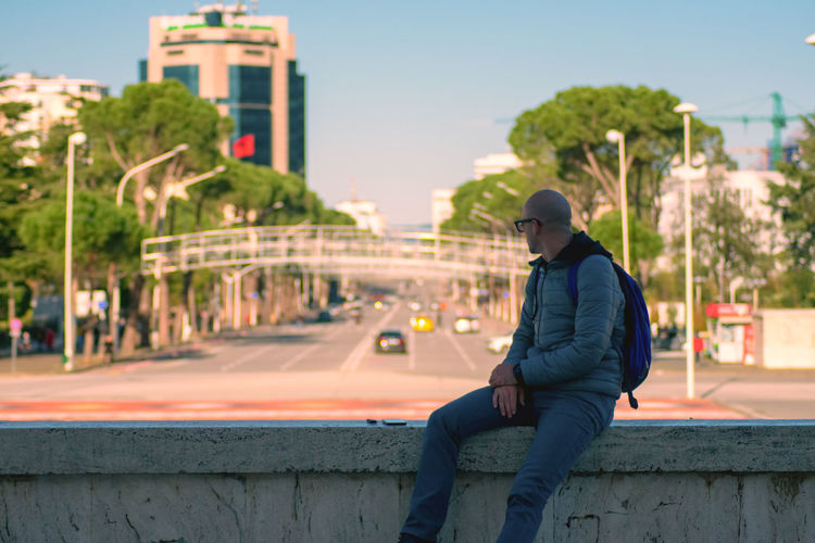 Man sitting on retaining wall in city against sky