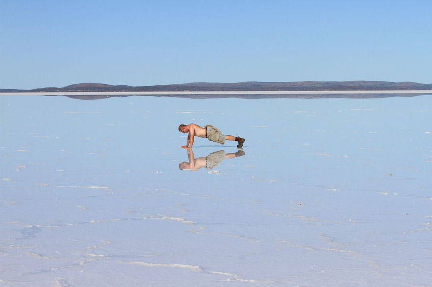 Finding yourself in the remotest of places! Adult Australian Outback Beauty In Nature Blue Blue Sky Day Flexibility Full Length Lake Gairdner Mirror Image Nature One Person Outdoors People Purple PushUp Real People Reflection Remoteness Salt Lake Shirtless Sky South Australian Outback Upside Down Water